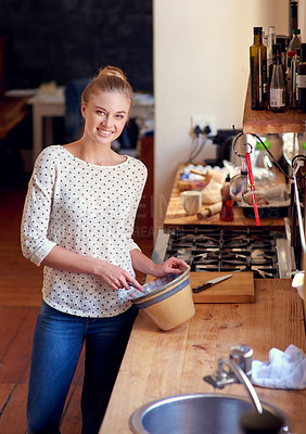 Buy stock photo Shot of a beautiful young woman preparing food in her kitchen