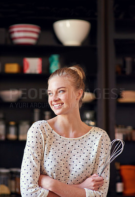 Buy stock photo Shot of a young woman standing with a whisk in her kicthen