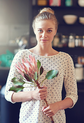 Buy stock photo Shot of a beautiful young woman standing in her kitchen holding a protea flower