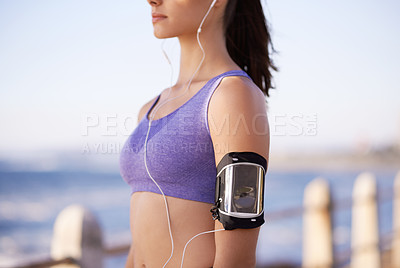 Buy stock photo Cropped shot of a sporty young woman listening to music while standing outdoors