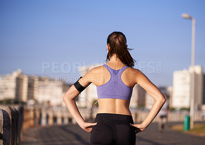 Buy stock photo Rearview shot of a sporty woman looking at the city