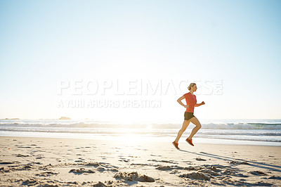 Buy stock photo Shot of a young woman running on the beach