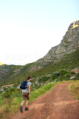 Buy stock photo Shot of a handsome young man enjoying a hike