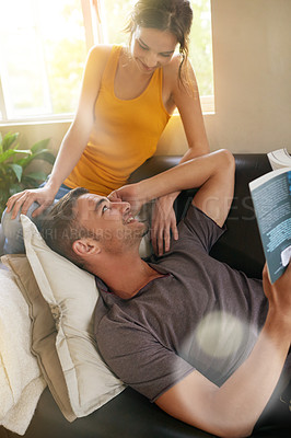 Buy stock photo Shot of a young man reading a book while relaxing on the sofa with his wife
