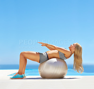 Buy stock photo Shot of an attractive young woman working out with an exercise ball by a swimming pool