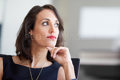 Buy stock photo Shot of an attractive businesswoman sitting in a chair in an office
