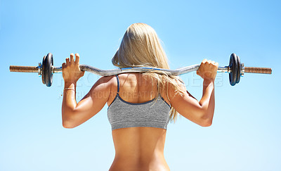 Buy stock photo Rearview shot of a young woman doing squats with a barbell outside