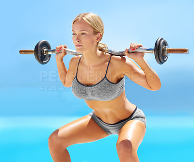 Buy stock photo Shot of an attractive young woman doing squats with a barbell outside