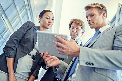 Buy stock photo Shot of a group of businesspeople discussing work on a digital tablet