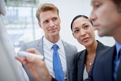 Buy stock photo A businessman drawing a diagram on a flip-chart as his colleagues stand by