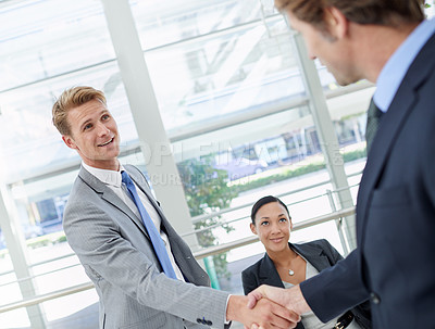 Buy stock photo Shot of two businessmen shaking hands in an office setting