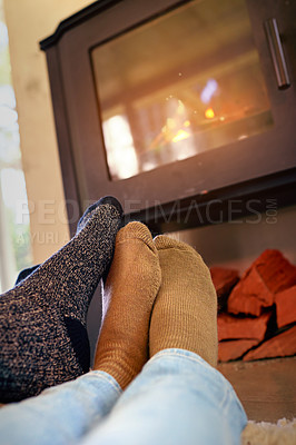 Buy stock photo Cropped shot of a couple sitting by the fireplace