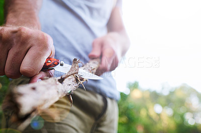 Buy stock photo Cropped shot of a man whittling  a branch