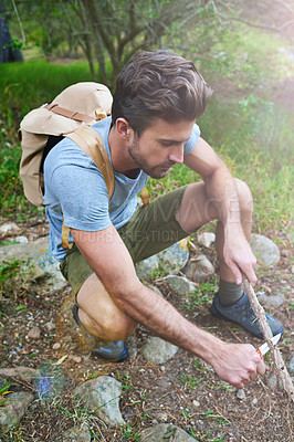 Buy stock photo Shot of a handsome hiker whittling a branch