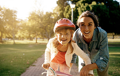 Buy stock photo Shot of a woman teaching her daughter how to ride a bicycle at the park