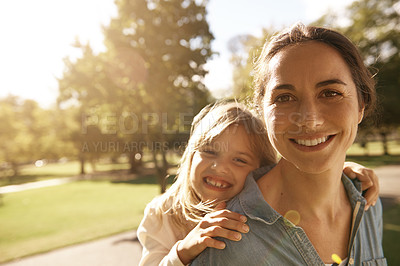 Buy stock photo Shot of a mother giving her daughter a piggyback ride at the park