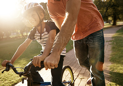 Buy stock photo Shot of a father teaching his son how to ride a bicycle at the park