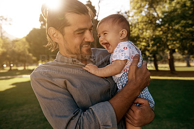 Buy stock photo A handsome young father spending time with his baby boy at the park