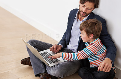 Buy stock photo A father and son sitting on the floor with a laptop