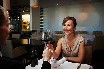 Buy stock photo Shot of a mature couple enjoying a glass of wine at a fine restaurant