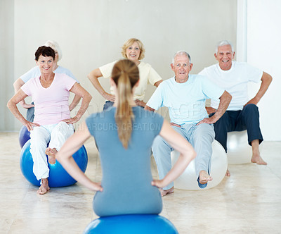 Buy stock photo A group of elderly people exercising together on balance balls