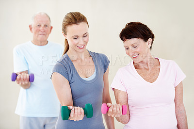 Buy stock photo An elderly woman lifting a dumbbell while being helped by her instructor