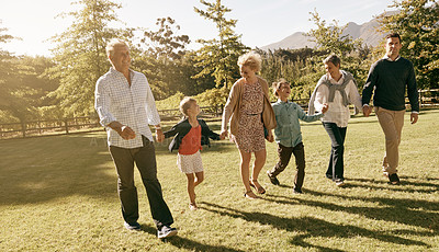 Buy stock photo Shot of a multi-generational family walking together in the outdoors