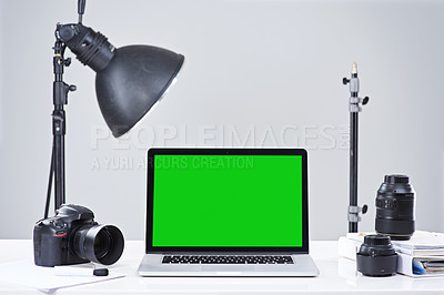 Buy stock photo Shot of a laptop with a green screen surrounded by photography equipment