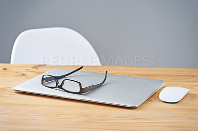 Buy stock photo Shot of a laptop and glasses on a table