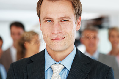 Buy stock photo Closeup portrait of a successful young businessman leading his successful team at office