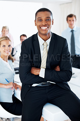 Buy stock photo Portrait of a smiling young businessman sitting on the desk and his team working behind at office