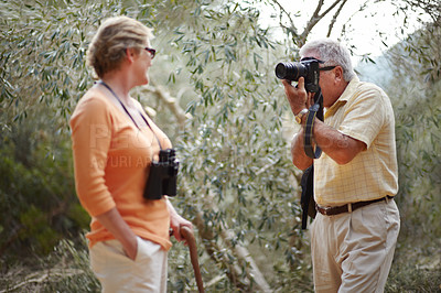 Buy stock photo Shot of a senior man taking a photo of his wife while they're on a nature hike