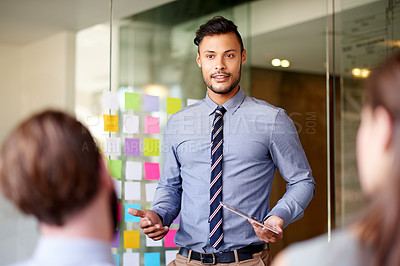Buy stock photo Shot of a young businessman giving a presentation to colleagues using a digital tablet