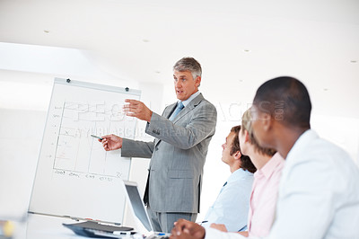 Buy stock photo Portrait of a senior manager giving presentation to his colleagues at office