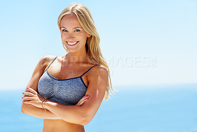 Buy stock photo Portrait of a beautiful blond woman in sportswear standing outside with the ocean in the background