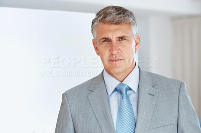 Buy stock photo Portrait of a successful mature businessman in suit standing confidently at office