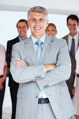 Buy stock photo Happy mature businessman standing confdently with colleague in the background