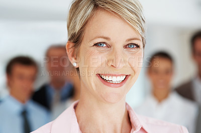 Buy stock photo Closeup portrait of a smart young businesswoman smiling and her colleagues at the back