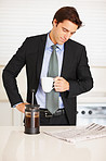 Young man reading newspaper while drinking coffee at home