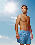 Shirtless young guy standing isolated against the blue sky