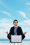 Business man sitting in lotus position with laptop on a pier