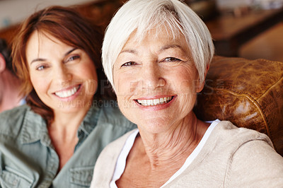 Buy stock photo Portrait of a young woman and her mother sitting on a sofa