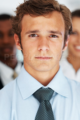 Buy stock photo Closeup portrait of confident young executive with businespeople in background