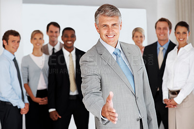 Buy stock photo Happy mature business man offering a welcoming hand with colleagues at the background