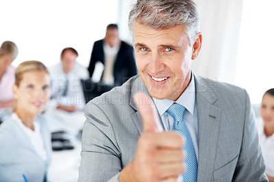Buy stock photo Portrait of a senior manager gesturing goodluck sign and his team working behind at office