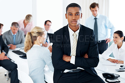 Buy stock photo An african american businessman sitting with his hands folded and his colleagues working behind