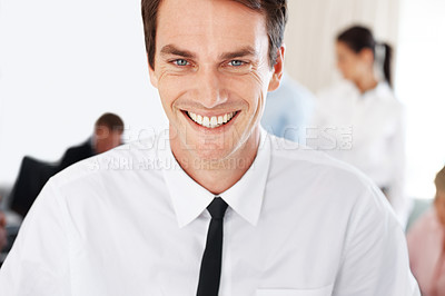 Buy stock photo Portrait of a successful male business executive smiling with colleagues in background