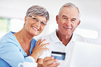Smiling mature couple shopping online