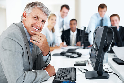 Buy stock photo Happy mature businessman at his desk with colleagues in the background