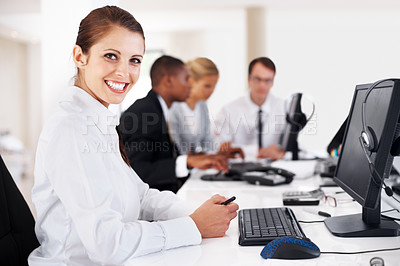 Buy stock photo Smart young businesswoman smiling with her team working in background